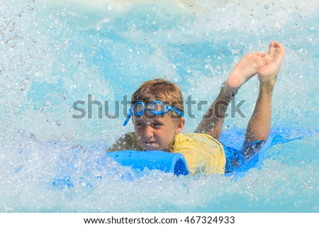 Rhodes,Greece-August 8,2016:The boy joying on the mat racer slide.Mat racer slide is very popular for young people in the Water Park. Water Park is located on the island of Rhodes in Greece