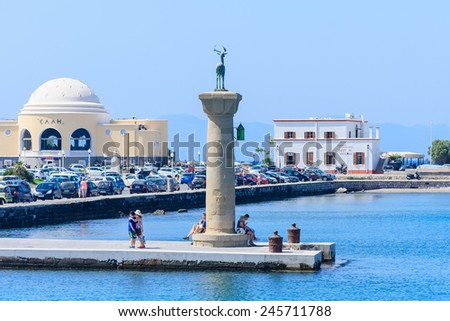 RHODES, GREECE - JUNE 28, 2014:  Tourists walking along Mandraki harbor with castle and famous deer statues at the island of Rhodes, June 28 2014, Greece - stock photo