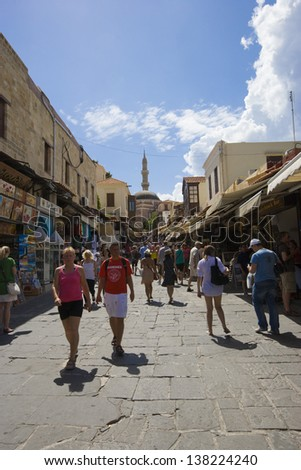 RHODES, GREECE - JUNE 23: Tourists walking along the stores of famous Socrates street at the old (medieval) town of Rhodes, one of the best preserved medieval cities in Europe, June 23 2010, Greece