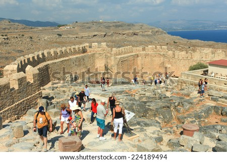 Rhodes, Greece - October 13, 2014: Tourists at the top of Lindos Acropolis ruins, a natural citadel which was fortified successively by the Greeks, the Romans, the Byzantines, and the Ottomans. - stock photo