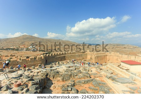 Rhodes, Greece - October 13, 2014: Tourists at the top of Lindos ancient Acropolis ruins, a natural citadel which was fortified successively by the Greeks, the Romans, the Byzantines,and the Ottomans. - stock photo