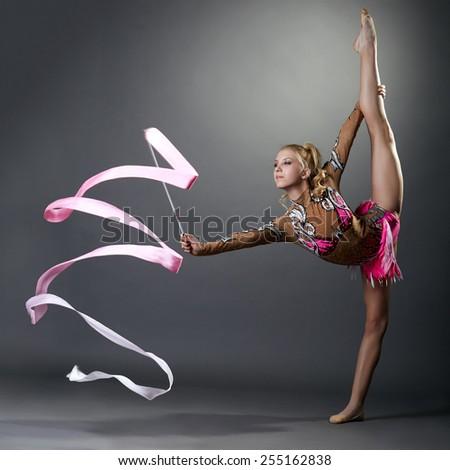 Rhythmic gymnast doing vertical split with ribbon - stock photo