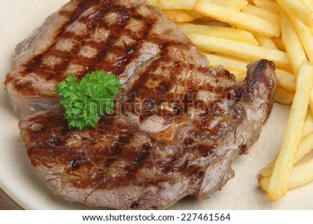 Rib-eye beef steak served with fries. - stock photo