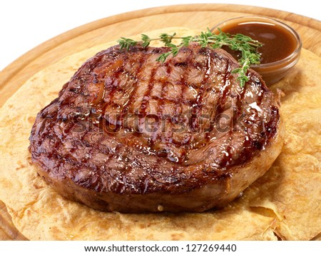 Rib-eye steak resting on the wooden plate - stock photo