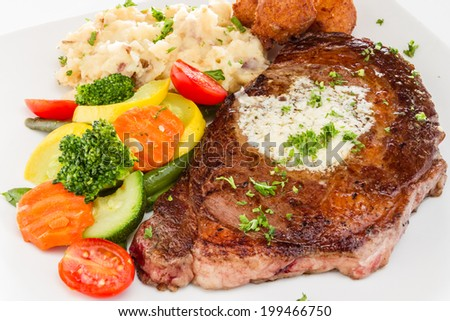 Rib-eye steak served with mashed potatoes, vegetable medley, and hush puppies. - stock photo