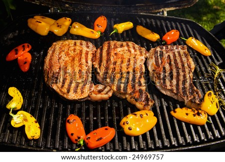 ribeye steaks cook on the barbque grill with baby bell peppers