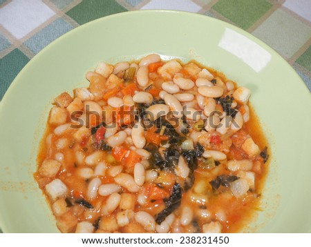 Ribollita meaning reboiled is a Tuscan soup made with bread and vegetables including leftover bread, cannellini beans, carrot, cabbage, beans, silverbeet, kale, and onion - stock photo