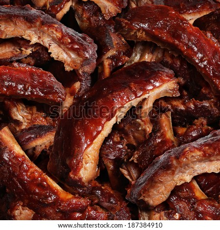 Ribs grilled barbecue meat with a close up view of a group of delicious cooked marinated spare rib as  gourmet food for dinner at a restaurant or backyard BBQ grill. - stock photo