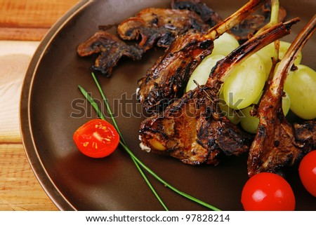 ribs on dish over wooden table with cherry