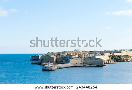 Ricasoli Grand Harbour East Breakwater and red lighthouse - stock photo