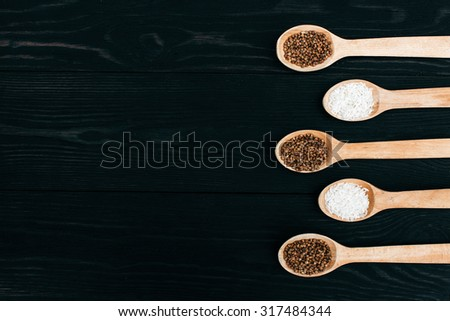 rice and buckwheat groats  in the wooden spoon on the black table - stock photo