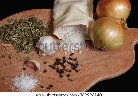 Rice and spices on a wooden cutting board - stock photo