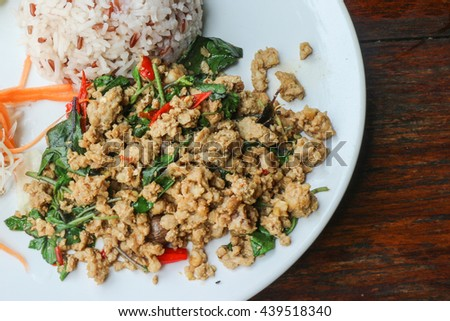 Rice and stir fried pork holy basil (Thai food) - Close up of rice topped with stir fried minced pork and holy basil - stock photo
