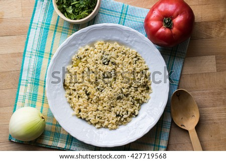 rice bulghur in the kithcen with vegetables on wooden surface top view - stock photo