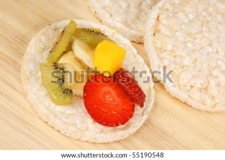 Rice cakes with fresh fruit slices, over a wooden background