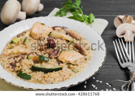 Rice cooked risotto with chicken meat and mushrooms and vegetables ingredients for risotto cherry tomatoes, zucchini squash, mushrooms, champignons, silver fork on a dark black wooden background - stock photo