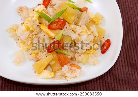 rice cooked with vegetables and chopsticks on brown  background closeup