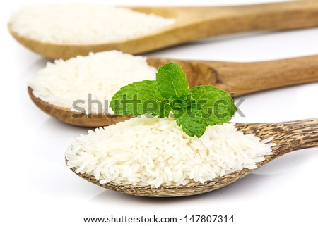 Rice grain on wooden spoon arrange in row on white background