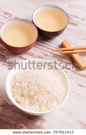 rice, green tea and chopsticks for sushi on white wooden background, top view, close-up, vertical