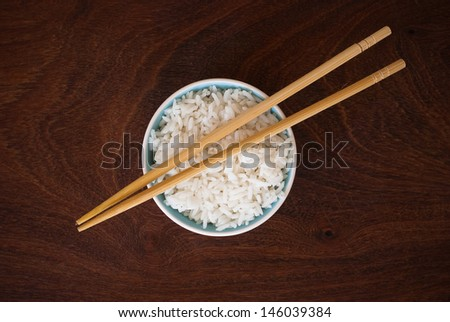 rice in a bowl and wooden chopsticks - isolated on wooden background - stock photo