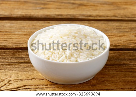 Rice in a bowl on wooden background - stock photo