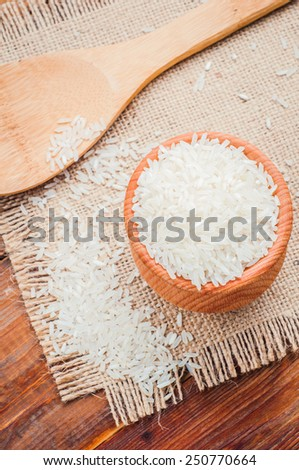 rice in a pot and spoon on burlap - stock photo