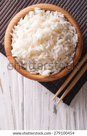 rice in a wooden bowl and chopsticks close-up. vertical top view  - stock photo