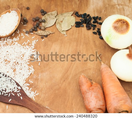 rice in a wooden spoon and scattered on the table, carrots, onions, spices, barberry, bay leaf on a table set for pilaf - stock photo
