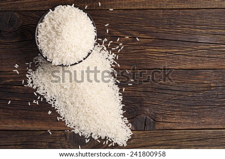Rice in black bowl and scattered near on dark wooden table, top view - stock photo