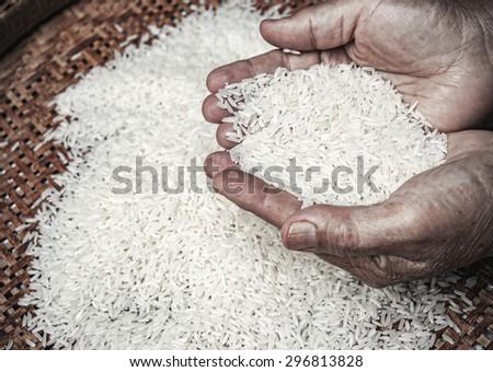 rice in hands of elder - stock photo
