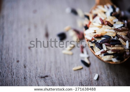 Rice in wood spoons - stock photo