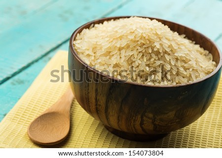 Rice in wooden  bowl on  blue wooden background. Selective focus. - stock photo