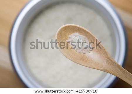 rice in wooden spoon. selective focus - stock photo