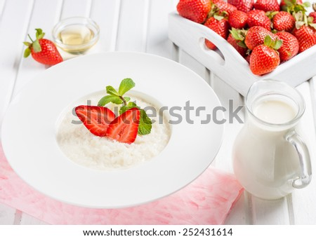 rice milk porridge with strawberries and mint on a white background