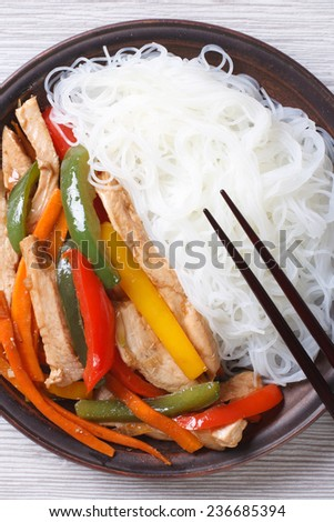 Rice noodles with chicken and vegetables macro on the table. vertical top view  - stock photo