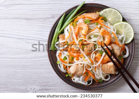 rice noodles with chicken, shrimp and vegetables close-up on a plate. horizontal view from above