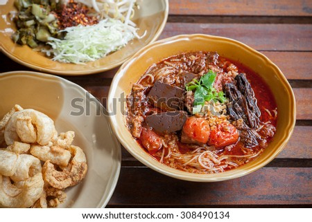 Rice noodles with spicy pork sauce (Nam ngiao) is a noodle soup or curry of the cuisine of the Tai Yai people. Nam ngiao has a characteristic spicy and tangy flavor. - stock photo