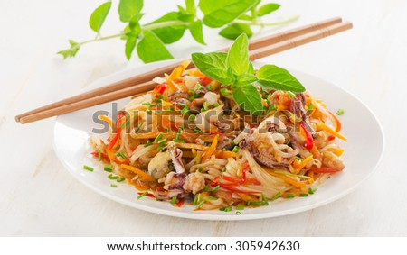 Rice noodles with vegetables and seafood on  a plate. Selective focus - stock photo