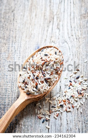 Rice on a wooden spoon  close up - stock photo