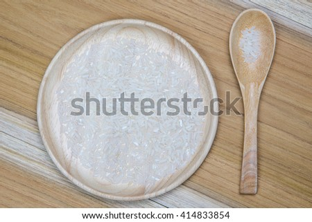Rice on wood bowl on wooden background. - stock photo