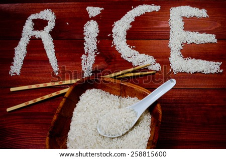 Rice on wooden table with chopsticks - stock photo