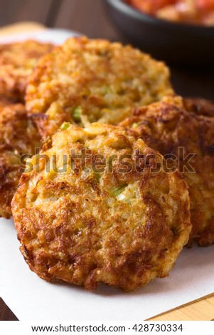 Rice patties or fritters made of cooked rice, carrot, onion, garlic and celery stalks, photographed with natural light (Selective Focus, Focus on the middle of the first patty) - stock photo