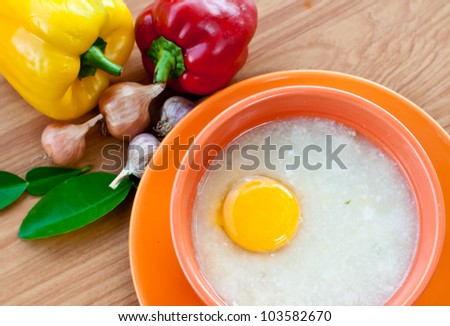 Rice porridge with egg in orange bowl on wood table with paprika and garlic.