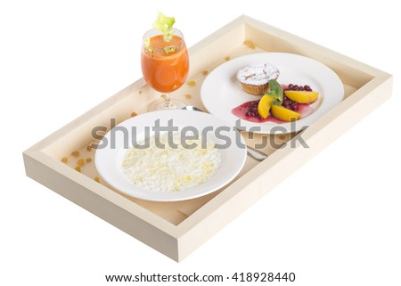 Rice porridge with muffin and juice on a wooden tray. Isolated on a white background.