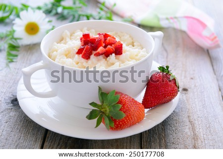 Rice porridge with slices of strawberry - tasty breakfast - stock photo