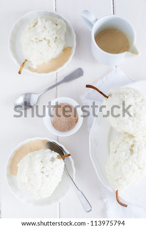 Rice pudding dessert with pears served with white dishes on white wooden background.