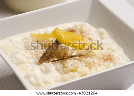 Rice pudding in a white bowl with lemon and grated cinnamon. Selective focus. Arroz con leche.