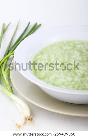 Rice pudding  in an individual bowl  with spring onion on white background