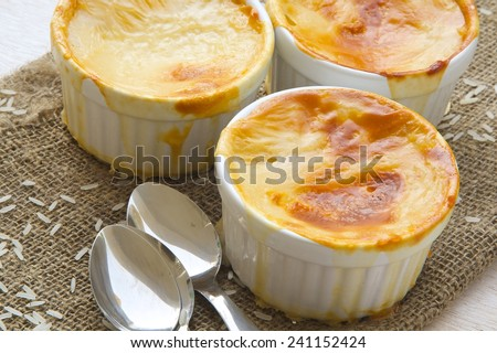 Rice pudding in ceramic moulds on sackcloth - stock photo