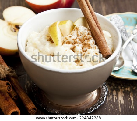 Rice Pudding with Apple Slices and Cinnamon Spice Sticks on Wooden Background